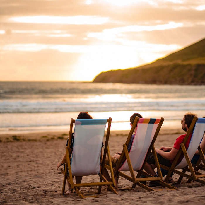 Three people in deckchairs at sunset