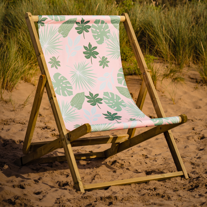 Botanical print pink giant deckchair with leaves on a beach. Monstera leaf design double deck chair.